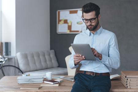 dia útil casual. homem jovem e bonito usando óculos e trabalhando com touchpad ao inclinar-se para a mesa no escritório