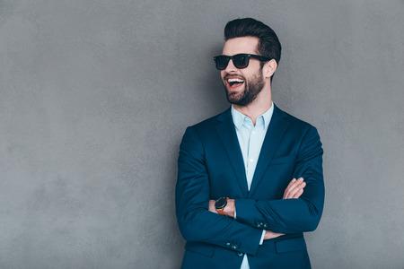 Stilvolle Lächeln. Fröhlich junger stattlicher Mann in den Sonnenbrillen Arme halten gekreuzt und suchen mit einem Lächeln weg, während, die gegen grauen Hintergrund Standard-Bild