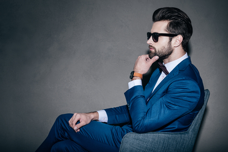 man in suit: All about style. Side view of young handsome man in suit and bow tie holding hand on chin and looking away while sitting in grey chair against grey background Stock Photo