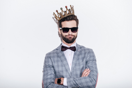 looking at: King of style. Sneering young handsome man wearing suit and crown keeping arms crossed and looking at camera while standing against white background Stock Photo