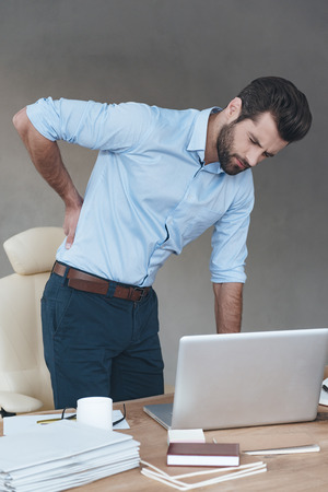 bending over: Back pain. Frustrated young handsome man looking exhausted while massaging his back and bending over the table at his working place  Stock Photo