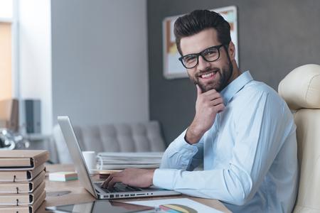 Zelfverzekerde en succesvolle. Zijaanzicht van knappe jonge man met een bril werken met laptop en kijken naar de camera met een glimlach tijdens de vergadering op zijn werkplek