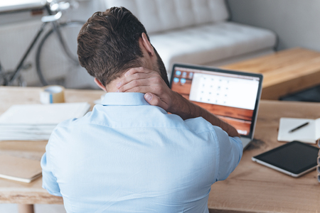Sentirse cansado. Vista trasera de un joven frustrado mirando agotado y masajear su cuello mientras estaba sentado en su lugar de trabajo
