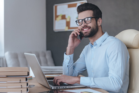 work worker: Great news! Handsome cheerful young man wearing glasses talking on mobile phone and looking away with smile while sitting at his working place Stock Photo