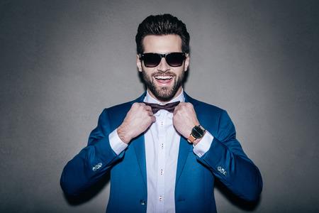 vistiendose: Siempre en buen estado de ánimo! Primer plano del hombre hermoso joven con gafas de sol alegre se ajuste a su corbata de lazo y mirando a la cámara con una sonrisa mientras está de pie contra el fondo gris