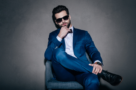 legs crossed at knee: Real macho. Young handsome man in sunglasses and suit keeping hand on chin and looking at camera while sitting on the chair against grey background Stock Photo