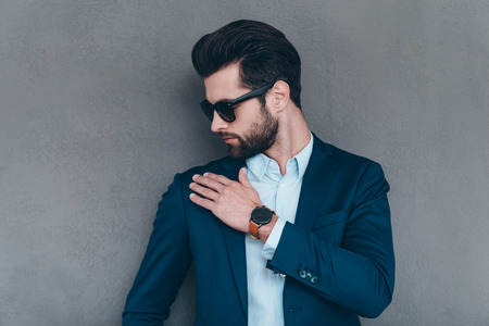 shake off: Shake it off. Close-up of young handsome man in sunglasses shaking off invisible dust from his shoulder while standing against grey background