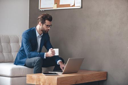 Começando novo dia de trabalho. Desgastando considerável do homem novo óculos segurando xícara de café e trabalhar com laptop enquanto está sentado no sofá no escritório