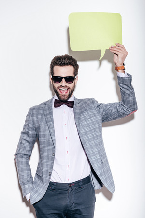 That is what I am saying. Handsome young cheerful man in suit looking at camera with smile and holding green speech bubble upon his head while standing against white background