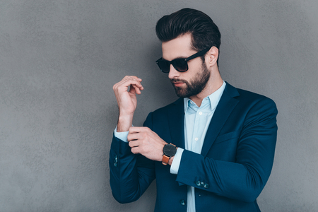 male fashion model: Everything must be perfect. Close-up of young handsome man in sunglasses adjusting sleeve on his jacket while standing against grey background