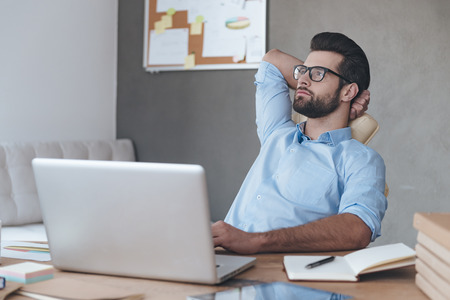 decisão de negócios todos os dias. homem bonito novo pensativo usando óculos mantendo a mão atrás da cabeça e olhando para longe, sentado em seu lugar de trabalho