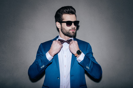model: Mr. Perfection. Close-up of handsome young man wearing sunglasses adjusting his bow tie and looking away while standing against grey background Stock Photo