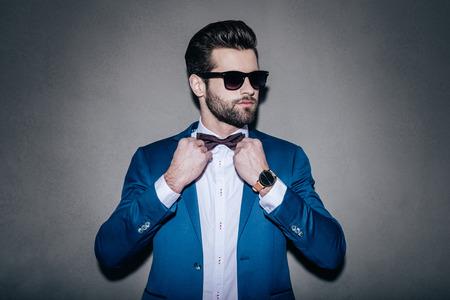Mr. Perfection. Close-up de bonito vestindo homem novo óculos de sol que ajusta sua gravata borboleta e desviando o olhar em pé contra um fundo cinza
