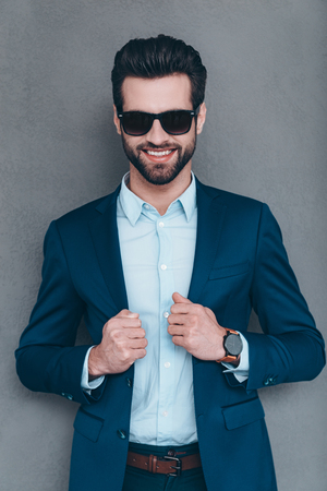 masculinity: Elegance and masculinity. Cheerful young handsome man in sunglasses keeping hand on his jacket and looking at camera with smile while standing against grey background