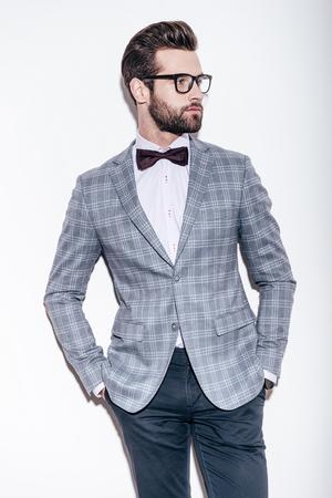 Le style et l'intelligence. Beau jeune homme portant le costume et des lunettes en gardant les mains dans les poches et en regardant loin tout en se tenant sur le fond blanc