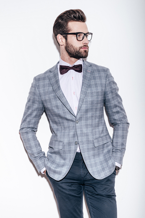 only one adult: Style and intelligence. Handsome young man wearing suit and glasses keeping hands in pockets and looking away while standing against white background
