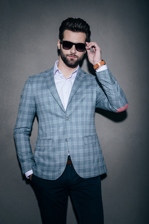 mr: Mr. Style. Handsome young man adjusting his sunglasses and looking at camera while standing against grey background