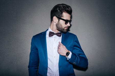 Herr Perfektion. Close-up der schönen jungen Mann mit Sonnenbrille seine Jacke anpassen und über die Schulter schauen, während sie gegen grauen Hintergrund