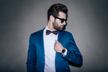 male fashion model: Mr. Perfection. Close-up of handsome young man wearing sunglasses adjusting his jacket and looking over his shoulder while standing against grey background Stock Photo