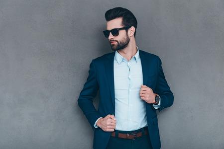 Elegante y exitosa. Hombre hermoso joven en gafas de sol de mantenimiento de la mano en la chaqueta y mirando a otro lado mientras está de pie contra el fondo gris Foto de archivo - 51617926