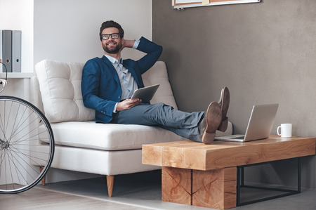 adults: Enjoying his working day. Handsome cheerful young man keeping legs on table and looking away with smile while sitting on the couch in office Stock Photo