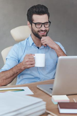 コーヒー ブレーク。眼鏡をかけて笑顔でラップトップに取り組んで、彼の職場で座ってコーヒー カップを保持している陽気な若いハンサムな男 写真素材