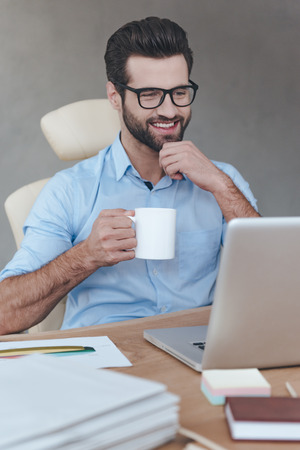 Coffee break. Cheerful young handsome man wearing glasses working on laptop with smile and holding coffee cup while sitting at his working place