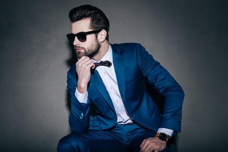 Style. Junger stattlicher Mann in Anzug und Fliege Hand auf Kinn und Wegschauen beim Sitzen vor grauem Hintergrund