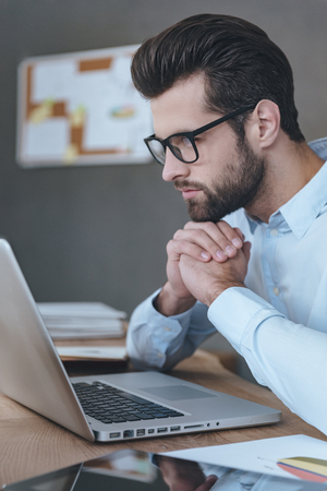 working on laptop: Double-checking his business plan. Side view close-up of handsome young man wearing glasses working with laptop while sitting at his working place