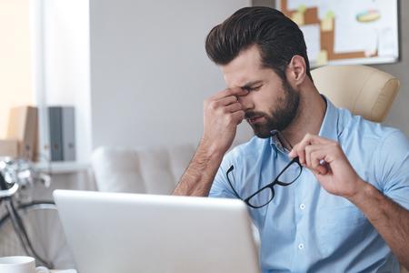 Sensación de cansancio. joven apuesto hombre frustrado que mira agota mientras se está sentado en su lugar de trabajo y llevando sus gafas en la mano Foto de archivo