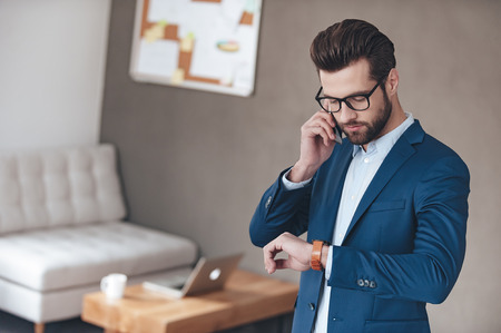 adults only: Checking his timetable. Handsome young man wearing glasses talking on mobile phone and looking at his wristwatch while standing in office