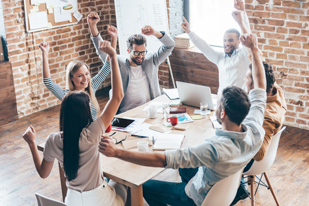 New achievement! Top view of group of six cheerful young people keeping arms outstretched and smile while sitting at the table in office  Stock Photo