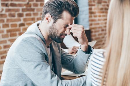 decepcionado: Sensación de cansancio. Primer plano de un hombre apuesto joven frustrado que mira agota mientras se está sentado en su lugar de trabajo en la reunión con sus compañeros de trabajo Foto de archivo