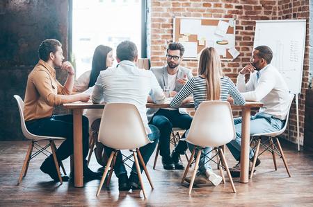 Reunión matutina. Grupo de seis jóvenes discutiendo algo mientras está sentado en la mesa en la oficina junto