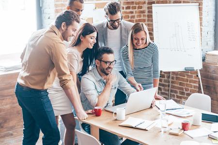 Tevreden met nieuwe plan. Groep van zes vrolijke jonge mensen kijken naar laptop met een glimlach terwijl leunt op de tafel in het kantoor