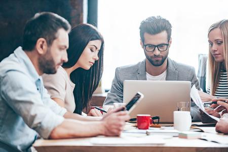 Haga doble comprobación de todos los documentos. Grupo de cuatro personas jóvenes que leen y miran a través de las cartas mientras se está sentado en la mesa en la oficina