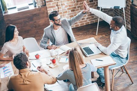 Toca aqui! Vista de cima de dois homens alegres jovens fazendo-high five, enquanto seus colegas de trabalho sentado na mesa do escrit