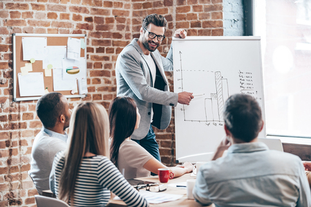 our company: Look how fast growth our company! Handsome young man in glasses standing near whiteboard and pointing on the chart while his coworkers listening and sitting at the table