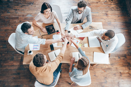 Starting new working day as a team. Top view of group of six young people holding hands together and smile while sitting at the office desk Фото со стока