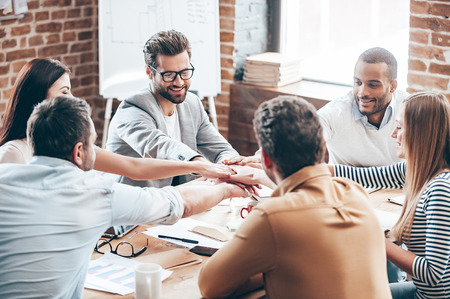 teamwork people: Perfect teamwork. Group of six young people holding hands together and smile while sitting at the office desk Stock Photo