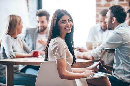 Fico feliz em ser uma mulher de negócios bem sucedido. Alegre jovem segurando laptop sobre os joelhos e olhando a câmera enquanto seus colegas discutindo algo em segundo plano Imagens