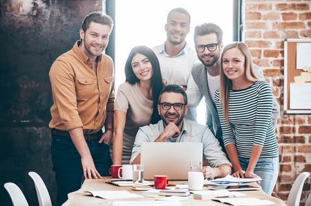 equipo creativo perfecto. Grupo de seis jóvenes alegres mirando a la cámara con una sonrisa mientras se inclina a la mesa en la oficina