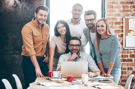 Perfect creative team. Group of six cheerful young people looking at camera with smile while leaning to the table in office Standard-Bild