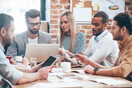 La búsqueda de nuevas ideas. Grupo de seis personas jóvenes que leen y miran a través de los documentos mientras se está sentado en la mesa en la oficina