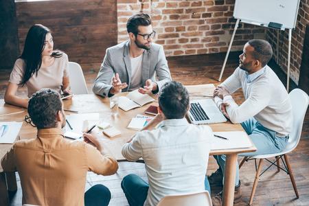 gente sentada: Dando algunos consejos a los compañeros de trabajo. Vista superior de jóvenes empresarios discutiendo algo mientras está sentado en el escritorio de oficina juntos Foto de archivo