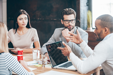 mujer pensativa: Discutir algunos asuntos de negocios. Grupo de jóvenes discutiendo algo mientras está sentado en la mesa de madera en la oficina
