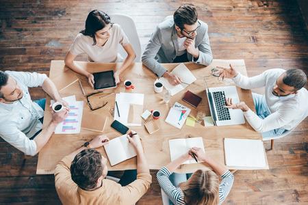 Ergebnisse und Teamarbeit. Draufsicht der Gruppe von sechs Menschen diskutieren etwas, während im Büro Tisch sitzen