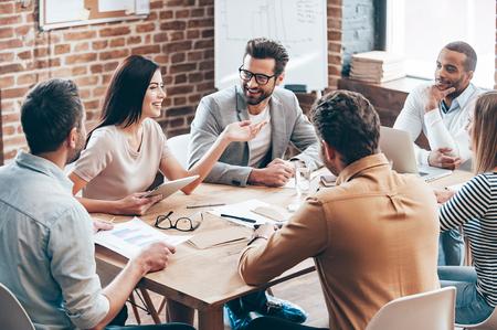 人々: 大きな決断を作る。若くてきれいな女性ジェスチャーおよび彼女の同僚は彼女のオフィスのテーブルの前に座って聴いてながら笑顔で何かを議論し