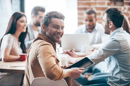 discussion: Glad to be a part of team. Cheerful young man holding digital tablet and looking at camera while his colleagues discussing something in the background  Stock Photo