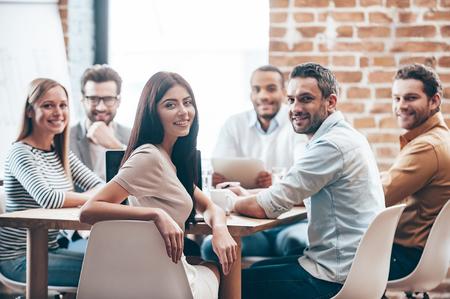 Perfect team. Groep van zes vrolijke jonge mensen op zoek naar camera met glimlach tijdens de vergadering op de tafel in het kantoor Stockfoto
